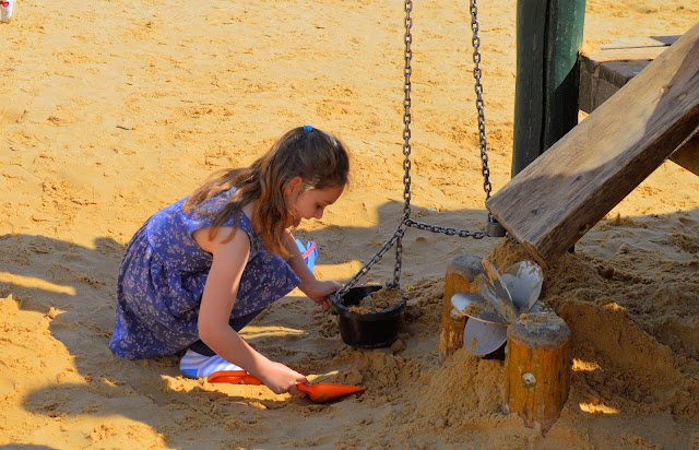 Girl building in sand