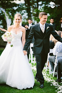 Laura and David smile widely as they leave their wedding ceremony