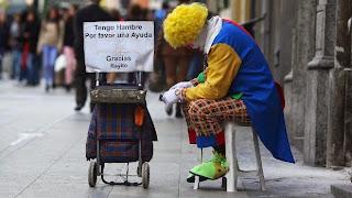 Ένας ζητιάνος ντυμένος ως κλόουν κάθεται στη Gran Via της Μαδρίτης και ζητά βοήθεια, επειδή πεινάει.
