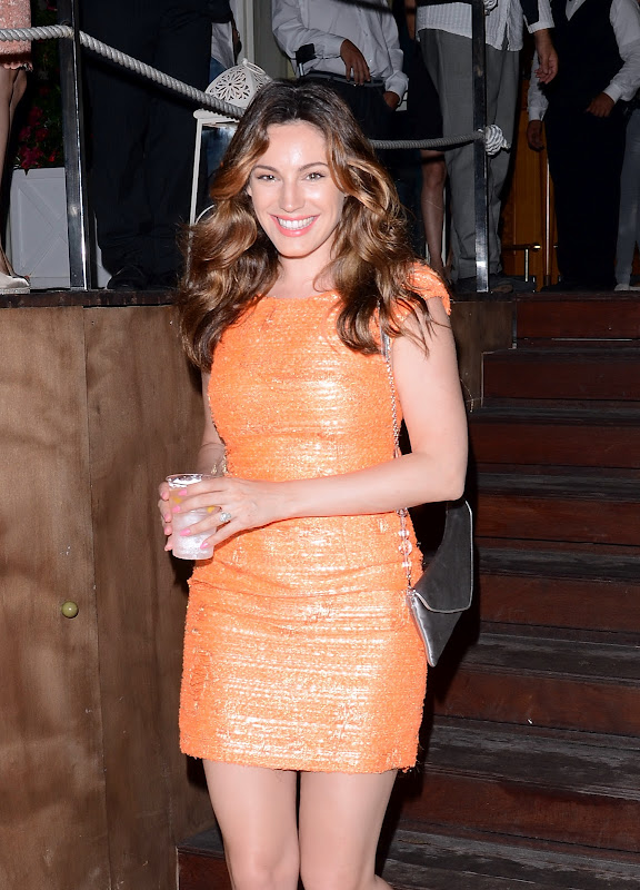 Kelly Brook ina tight orange dress holding a drink