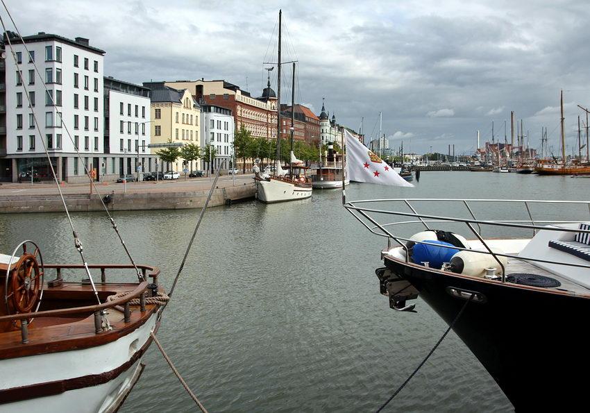 Paisagem da marina por ente a pro a a ré de dois barcos ancorados, revelando a margem oposta. com mais barcos e os prédios à beira de água