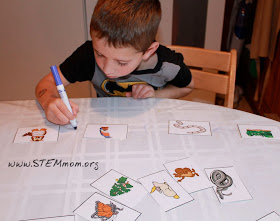 Boy drawing arrows in STEM Mom's Food Chain Activity