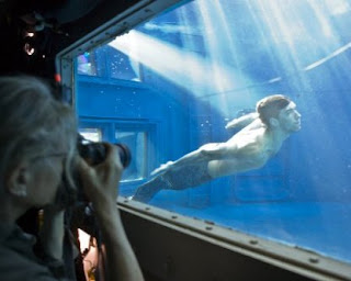Image: Leibovitz photographs Phleps, swimming his merman suit, through an aquarium window.