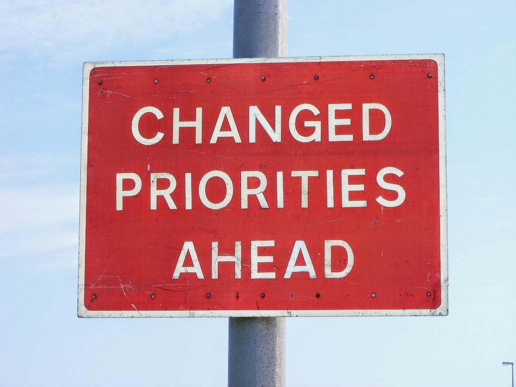"""Changed Priorities Ahead"" road sign"