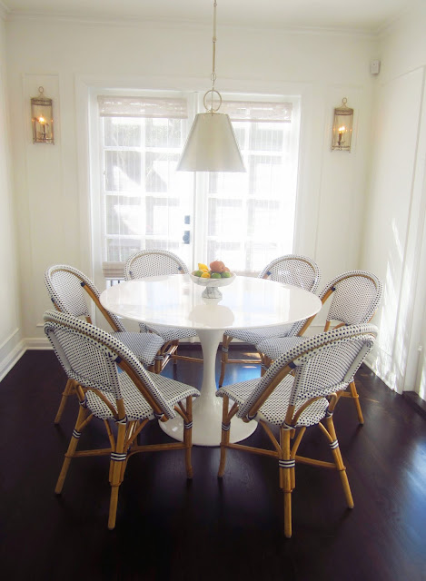 breakfast nook with white saarinen tulip table, blue and white french cafe chairs, silver pendant light, and dark wood floors