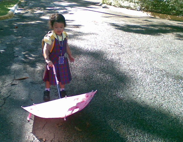 Kecil playing with her umbrella in school uniform