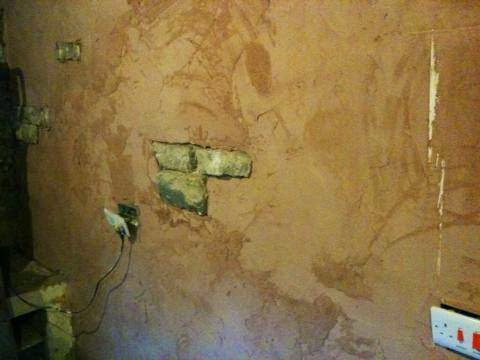 Plastering over old crumbling walls.