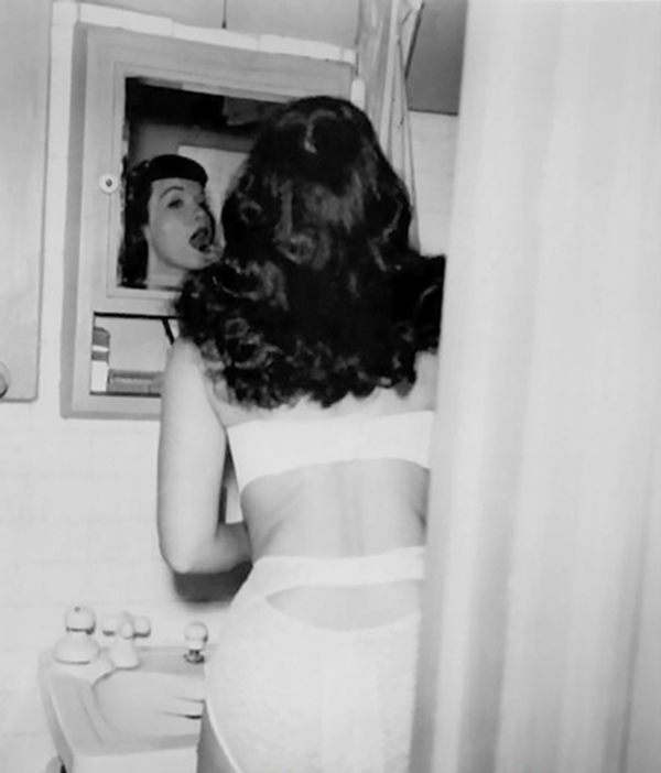 a candid photo of bettie page putting on lipstick