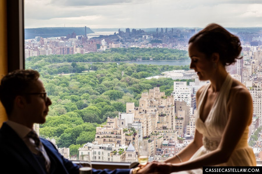 Silhouette of bride and groom sitting by window overlooking Central Park in the summer. NYC Lifestyle wedding photography by Cassie Castellaw. www.cassiecastellaw.com