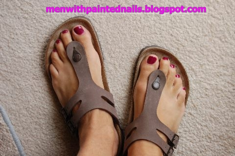 red painted toes on a man with birkenstock sandals