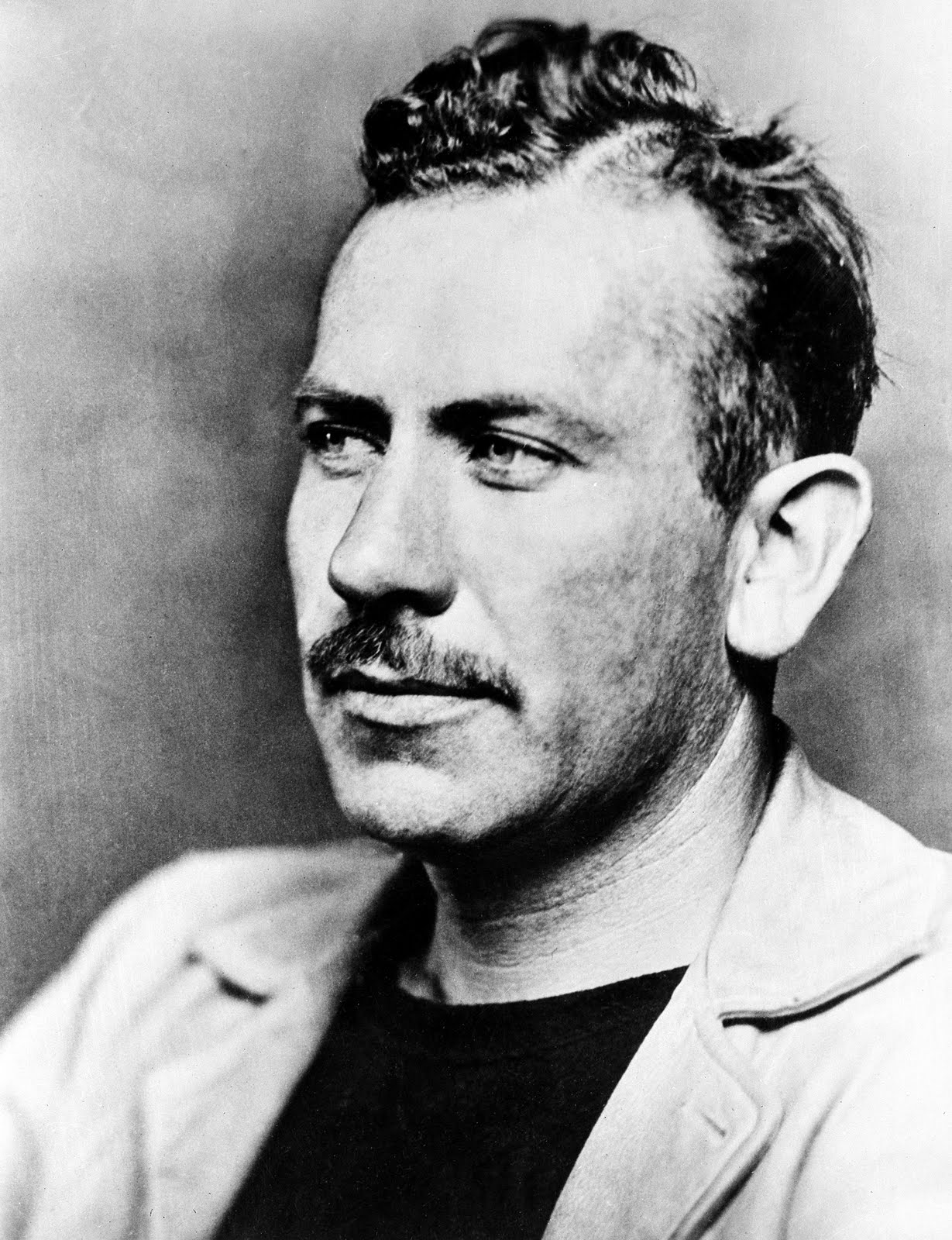 How does John Steinbeck use social realism in The Grapes of Wrath?