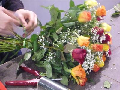 Ein Blumenstrauß mit Rosen wird gebunden