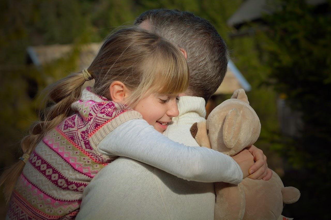 Vater kuschelt mit seiner Tochter