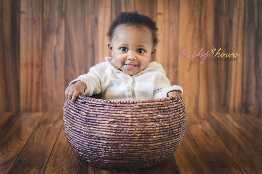 six month old boy photography session sitting in basket smiling