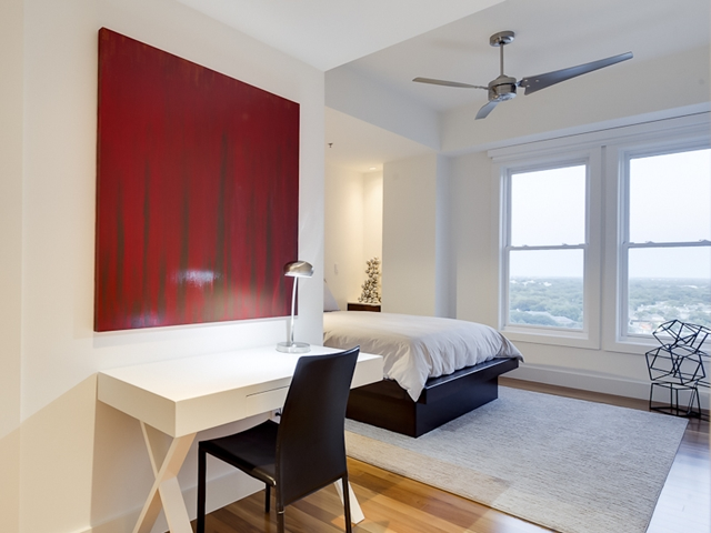 Photo of bedroom with red painting on the wall and working desk