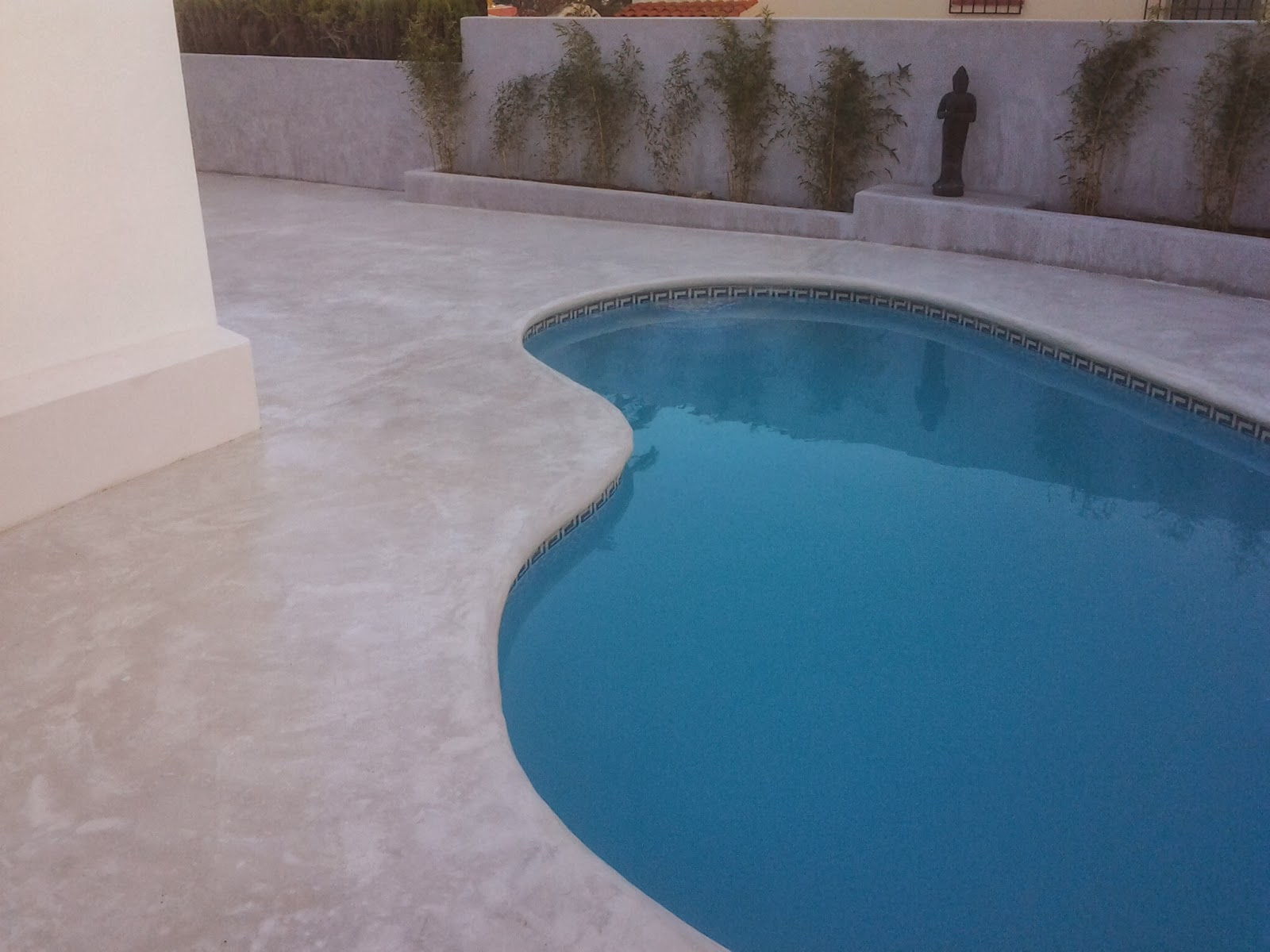 Piscina con pavimento continuo de hormig n en color blanco for Borde piscina hormigon