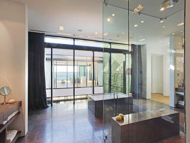 master bath room with glass walls, a stand alone tub, floor length curtains and a burgundy tile floor