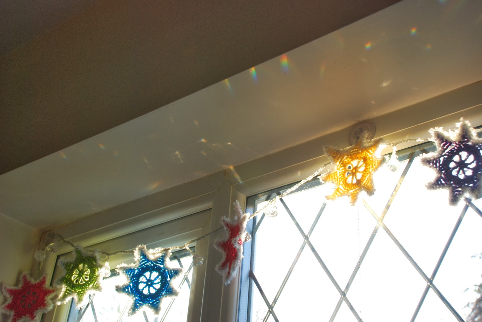 image of winter garland and crystal drop fairy lights producing rainbowsin the sunshine