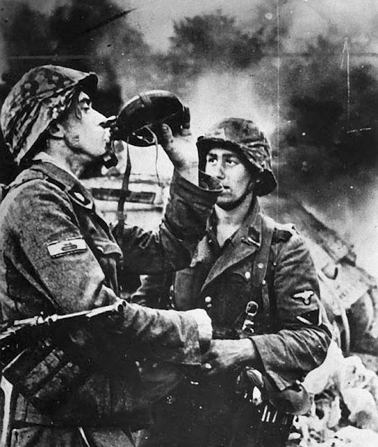 Two Waffen SS soldiers have a drink. In the background burns a T-34 tank
