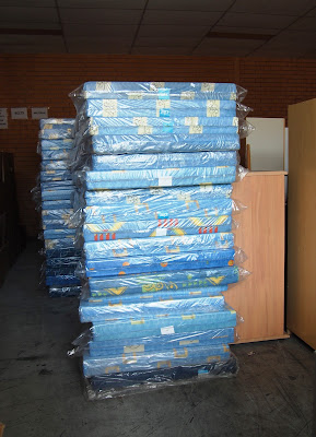 A stack of foam mattresses in plastic packaging.