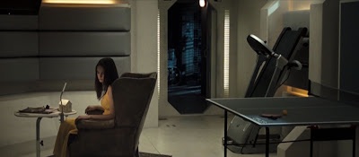dark haired woman sitting in an armchair in a recreation room