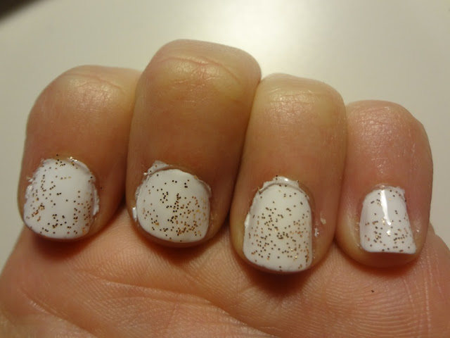 white nail polish with gold glitter over it