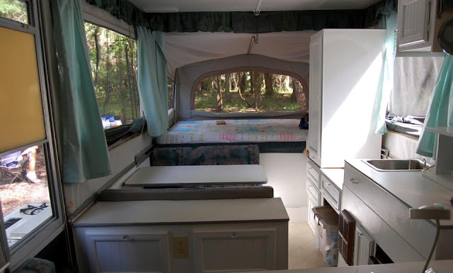 Jayco Pop Up Camper remodel in progress, white paint and white hardware goes a long way towards making this camper light, bright, and more modern, the bed quilt is fitted for a polished look all day long