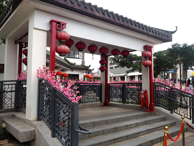 Chinese style pagoda / pavilion with red lanterns and pink blossom in Ngong Ping village, Lantau Island, Hong Kong