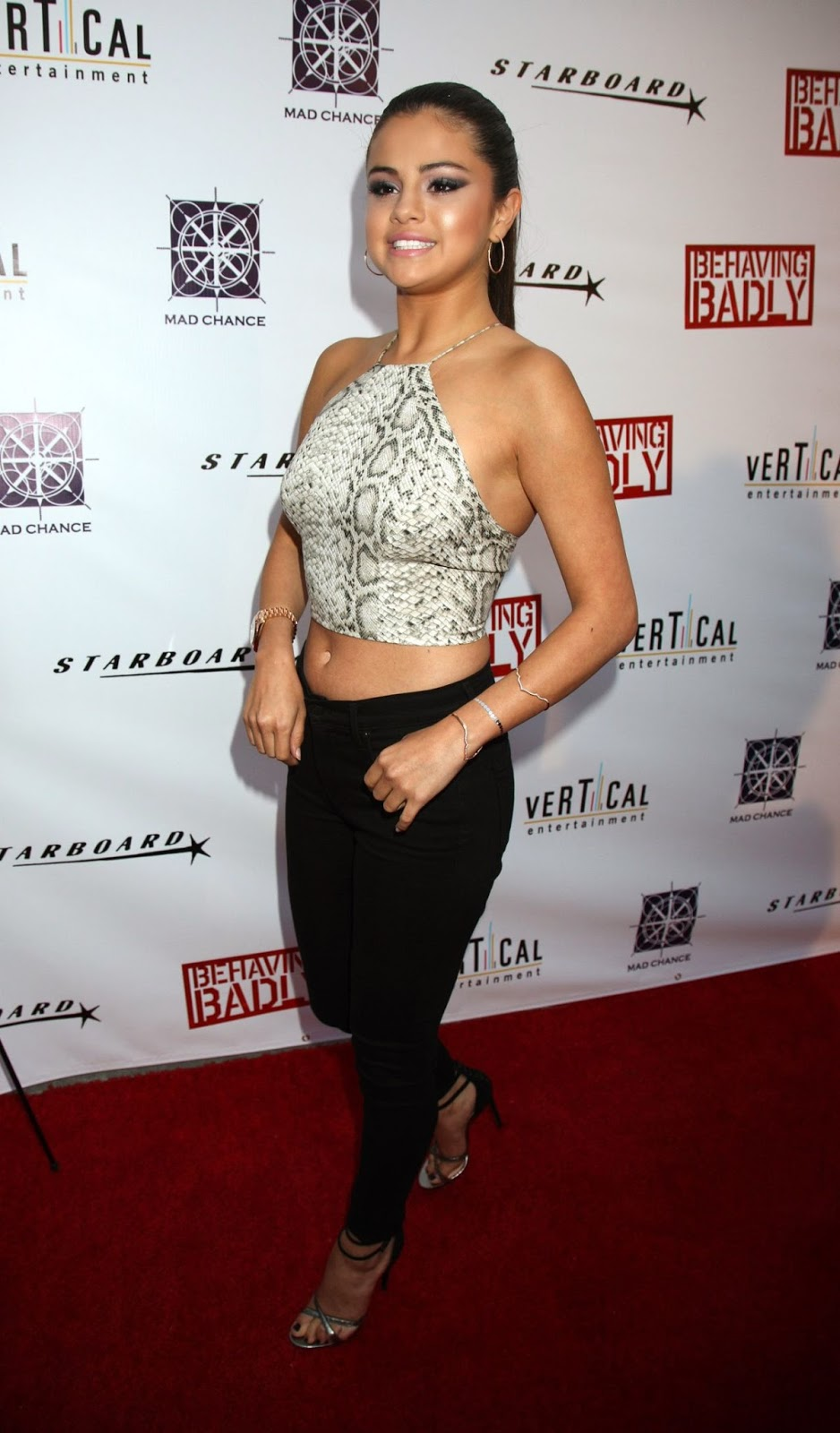 Selena Gomez shows toned midriff in a snakeskin cropped top at the 'Behaving Badly' Hollywood premiere