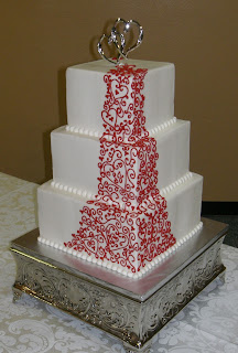 3 tier wedding cake with red scrolls and hearts