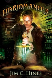 Cover of Libriomancer shows a pale-skinned, blond man pulling a sword out of a book, surrounded by sparkles and rays of light. A flaming spider perches on his shoulder.