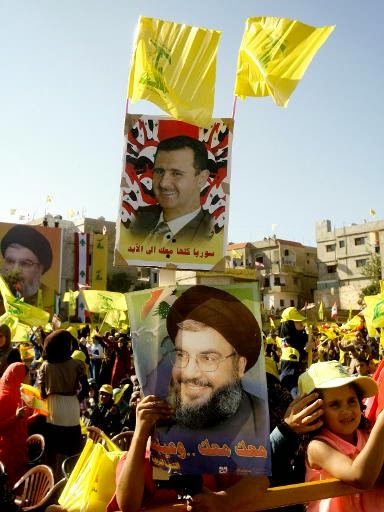 Picture taken on August 16, 2013 shows an image of Hezbollahs  leader Hasan Nasrallah (bottom) and Syrian President Bashar.  Mahmoud Zayyat/AFP/File.