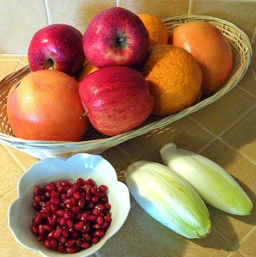 Basket of apples, mandarins, and grapefruit, bowl of pomegranate seeds, two endives