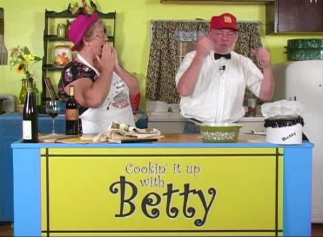 Betty tries her best to cook while bumbling Ronny tries to help.