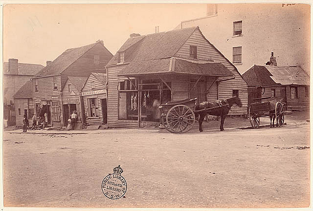 [Weatherboard buildings, Market Street, at the corner of Clarence Street, Sydney], [Dec 1875] / by unknown photographer. Notes: This photograph accompanied a scathing Government report into the city's sewerage system. Of these dwellings, it said, 'Any one who may be curious to know how long Colonial timber will last, until, by the combined action of the elements, white ants, and other sources of destruction, it becomes triturated into powder, can satisfy their curiosity by ascertaining the date on which these houses were constructed. The corner house is occupied and used as a butcher's shop; it is a filthy stinking place...'