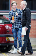 . comfortably driving exam DVLA driving test centre, Niall wearing jeans .