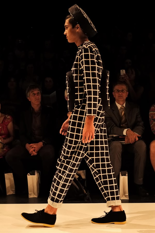 Matiny Ng; black and white criss-cross pattern with large raised circle motif on front and back of one-piece pant-suit with matching hat; side view - Menswear : Raffles Graduate Fashion Parade 2013 Photography by Kent Johnson.