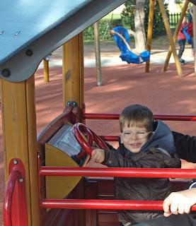un niño sonríe, jugando a conducir un coche en un parque infantil