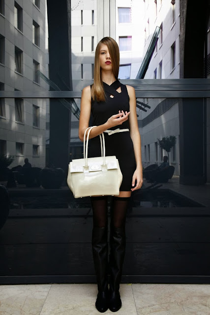 Beautiful combination of black dress , white bag and long leather boots