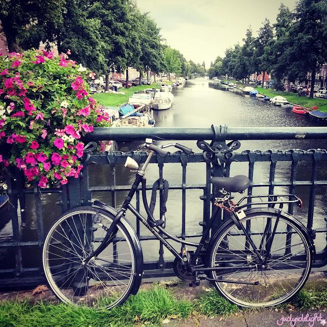 Blumen, Fahrrad auf einer Brücke im Hintergrund Hausboote.