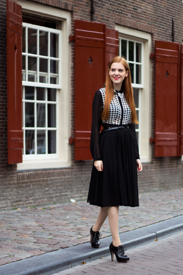 Chique fashion blogger outfit with a houndstooth blouse, midi skirt and heels