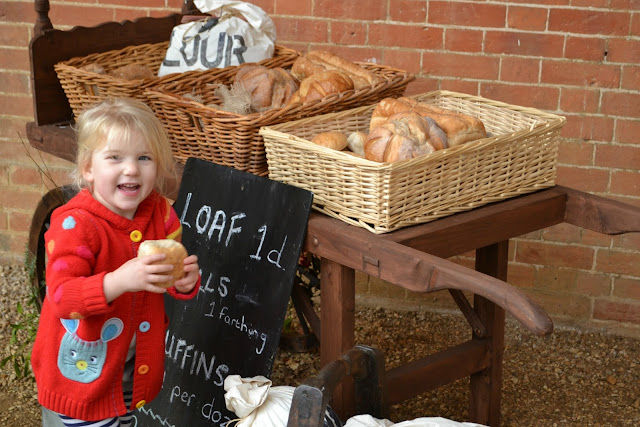 Tin Box Tot looks at bread in a market cart at Mottisfont Abbey