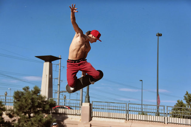 A skateboarder flying through the air during a jump at the Denver skate park.