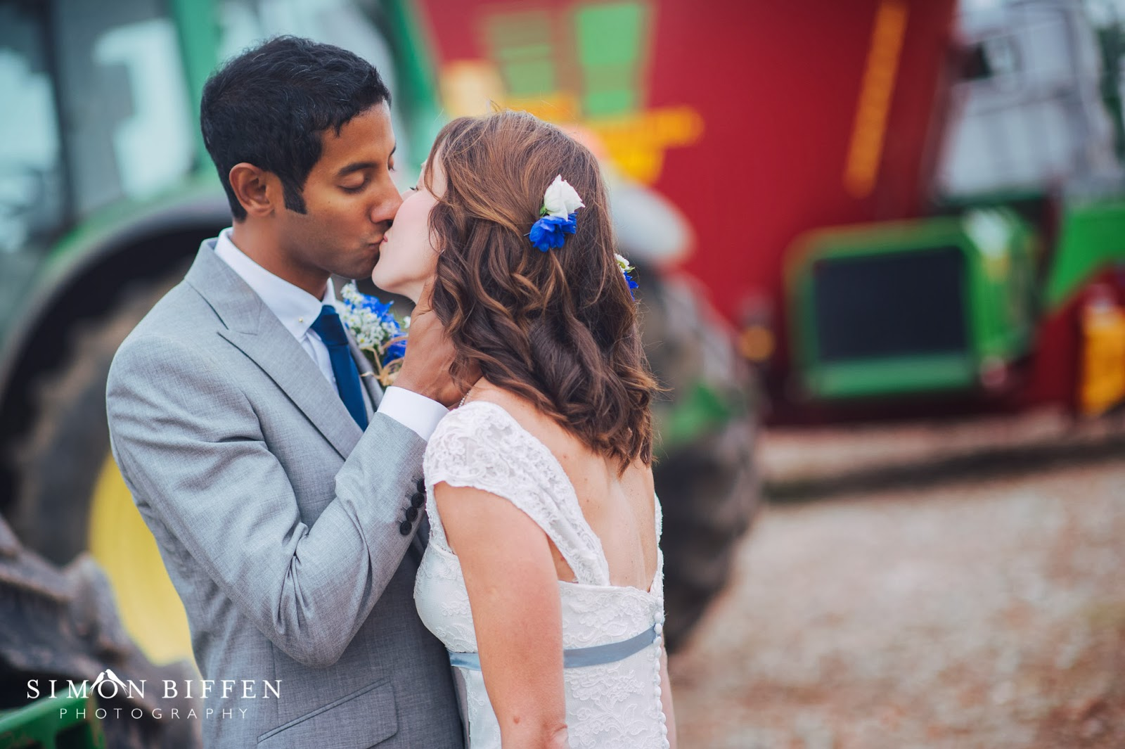 Bride and groom kiss between tractors at Quantock Lakes wedding