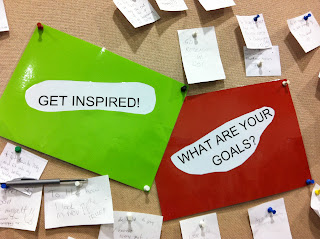 The notes stuck to the pinboard say GET INSPIRED and WHAT ARE YOUR GOALS?
