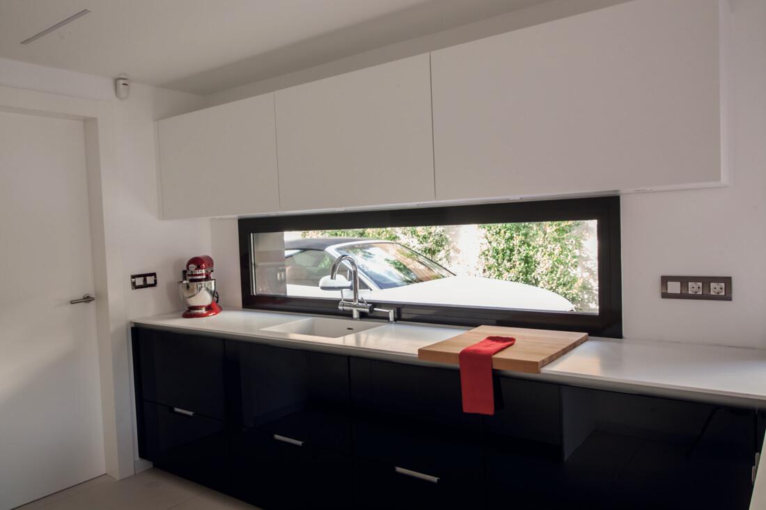 Una cocina en blanco y negro con pen nsula y office for Como desatascar un fregadero muy atascado