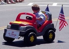 A boy is distracted while driving a toy car.