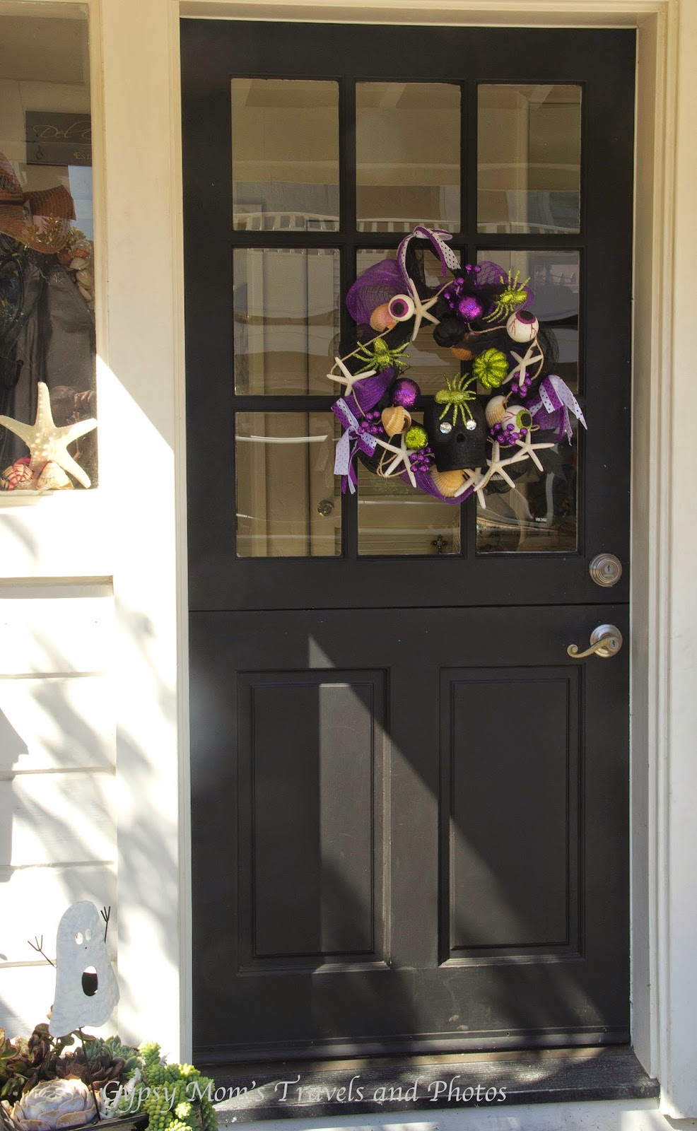 Black front door with wreath on house on Balboa Island