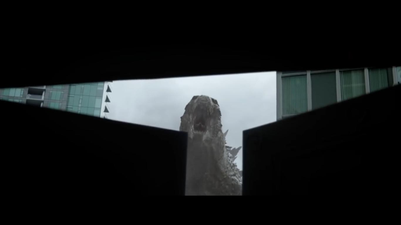Godzilla, viewed through closing double doors, screaming at the camera.