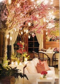 Faux cherry trees in bloom, strung with lanterns, flank a white couch in a room that is half-forest, half dinning room.